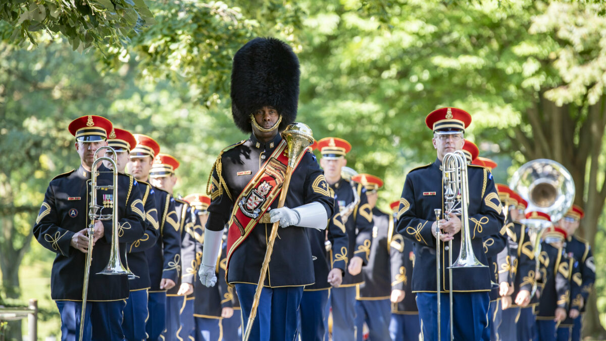 The U.S. Army Ceremonial Band marches beneath green trees.