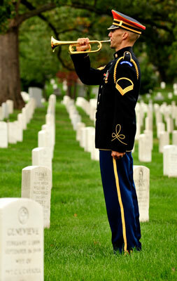A bugler from The U.S. Army band performing at Arlington National Cemetery